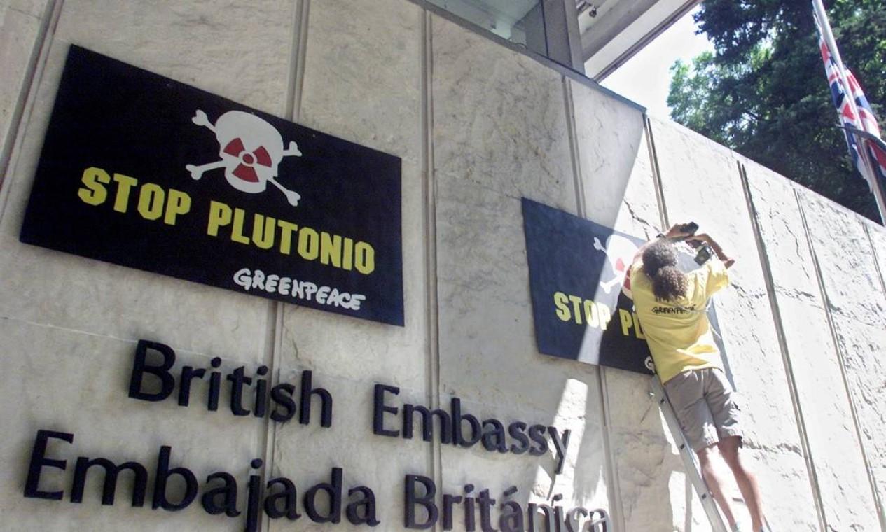 """Ativista do Greenpeace afixa um cartaz em frente à embaixada britânica, em Buenos Aires, exigindo às autoridades que não naveguem o navio britânico """"Pacific Swan"""" no Atlântico Sul. O Pacific Swan, que saiu da França rumo ao Japão, navega com uma carga de mais de 80 toneladas de resíduos nucleares Foto: Enrique Marcarian / Reuters - 05/01/2001"""