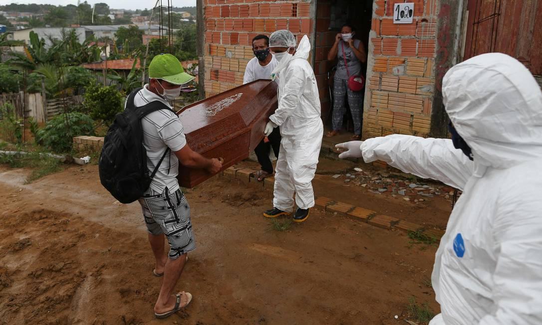 Agentes funerários removem caixão de idoso morto pela Covid-19, em Manaus, Amazonas, em maio de 2020. Foto: MICHAEL DANTAS / AFP