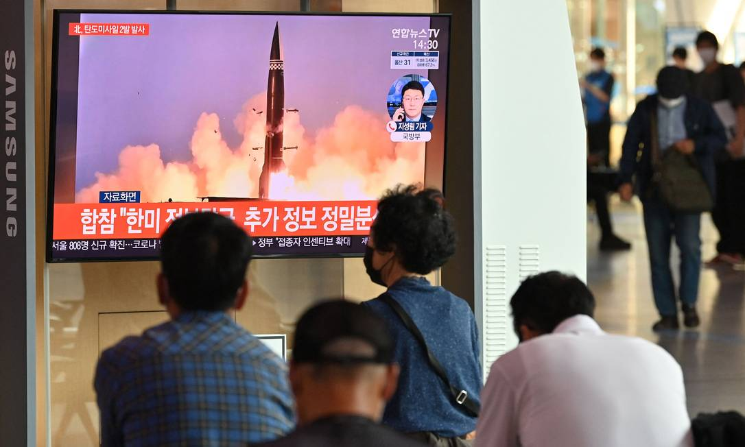 Pessoas assistem a um noticiário de TV mostrando imagens de um teste de míssil norte-coreano, em Seul, Coreia do Sul Foto: JUNG YEON-JE / AFP