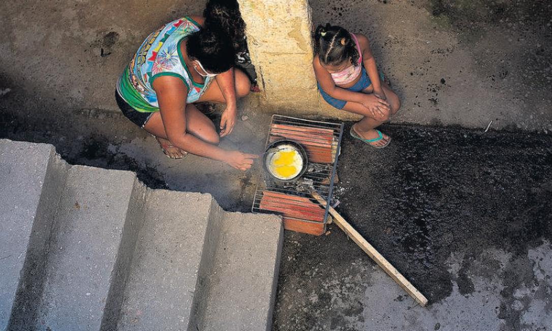 Rayane Oliveira, de 24 anos, economiza o gás, que não dá para o mês inteiro, cozinhando sobre dois tijolos com uma grade por cima Foto: Márcia Foletto