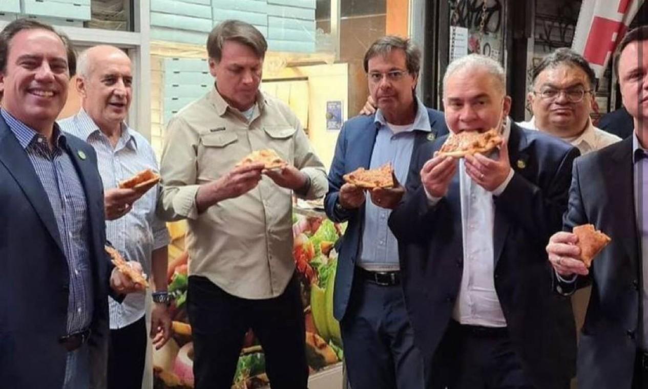 Bolsonaro come pizza na calçada em Nova York, com ministros, em setembro: sem estar vacinado, presidente não poderia entrar em restaurantes da cidade Foto: Reprodução