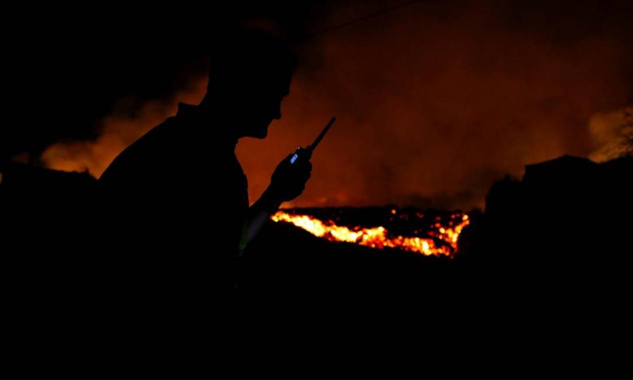 A lava flui ao lado de um policial local após a erupção de um vulcão no parque nacional Cumbre Vieja, em El Paso, nas ilhas Canárias Foto: BORJA SUAREZ / REUTERS