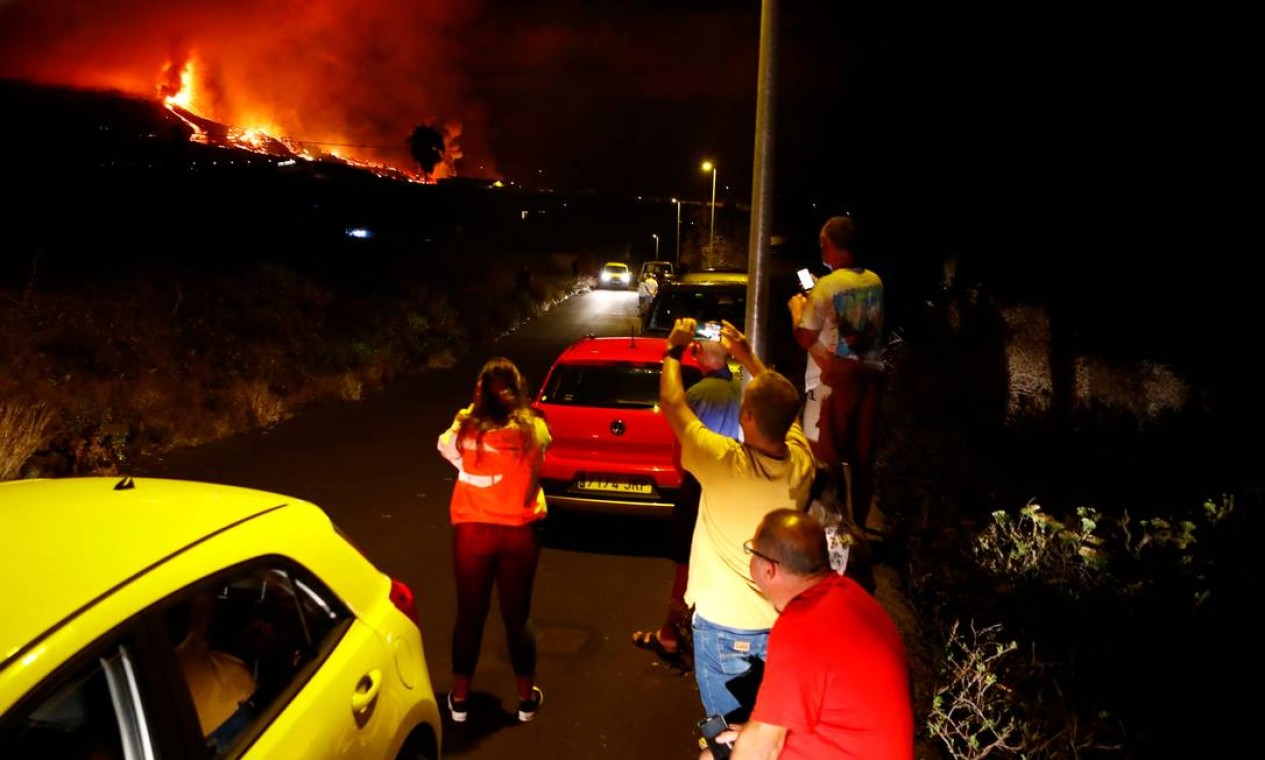 Moradores assistem a lava jorrar após a erupção do vulcão Cumbre Vieja, em El Paso Foto: BORJA SUAREZ / REUTERS