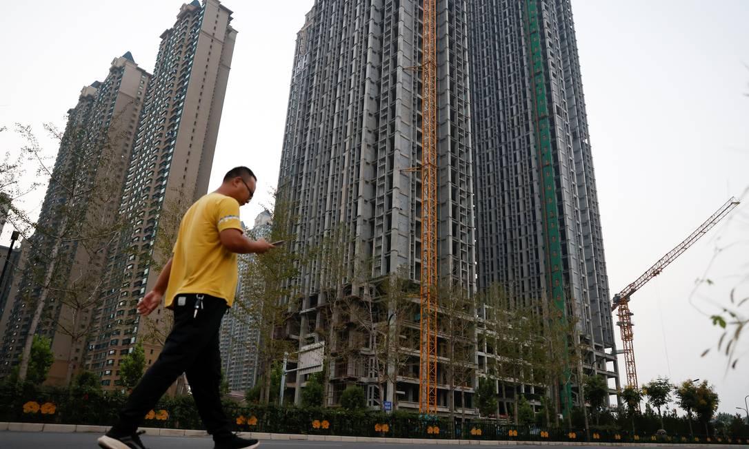 Homem passa em frente a condomínio desenvolvido pela chinesa Evergrande, em Guangzhou, no sul da China: empresa deve dar calote em investidores, fornecedores e clientes Foto: CARLOS GARCIA RAWLINS / REUTERS