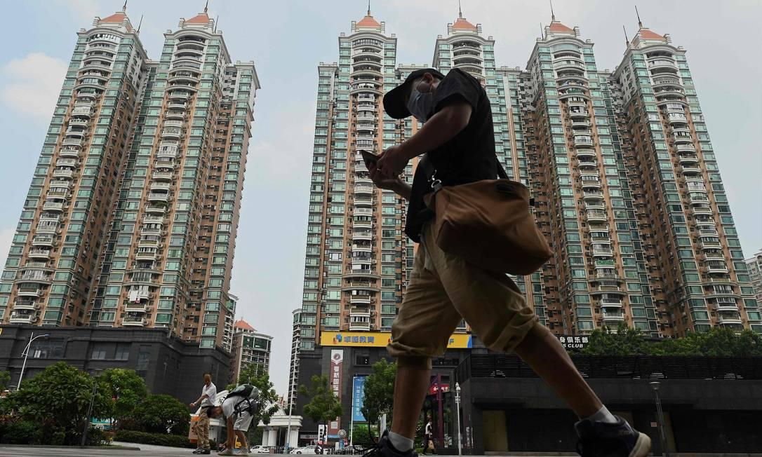 Homem passa em frente a condomínio desenvolvido pela chinesa Evergrande, em Guangzhou, no sul da China: empresa deve dar calote em investidores, fornecedores e clientes Foto: NOEL CELIS / AFP