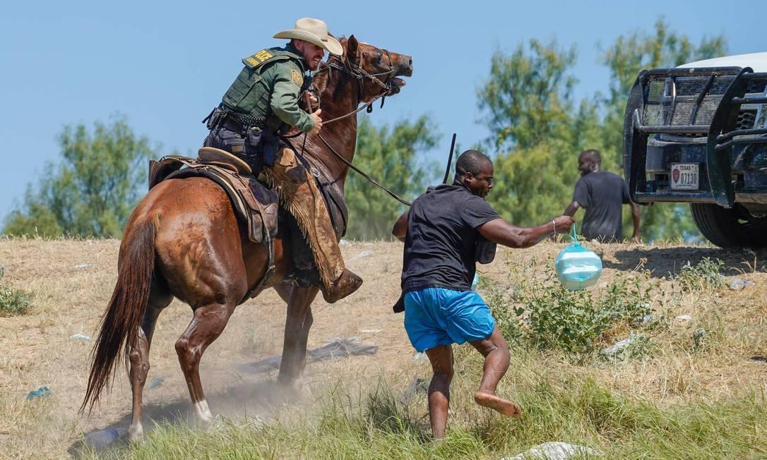 Integrante da patrulha de fronteiras dos EUA, montado em um cavalo, tenta impedir que imigrante haitiano chegue a uma margem do Rio Grande, perto da divisa com o México Foto: PAUL RATJE / AFP