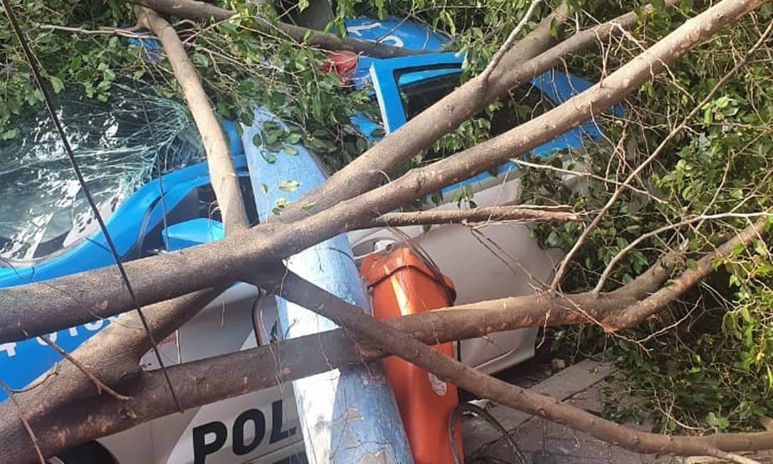 Em dia de ventania no Rio, poste atingido por árvore cai em cima de viatura da PM. Foto: Reprodução