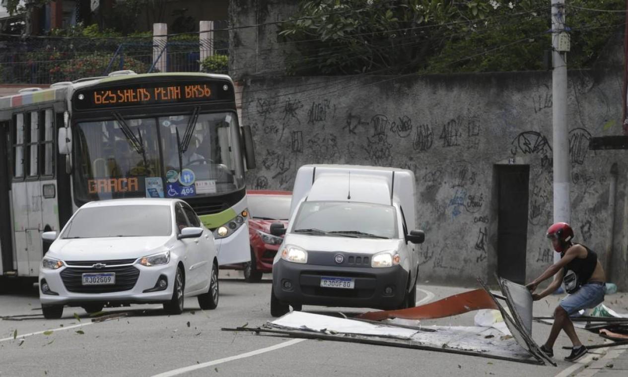 Motociclista retira pedaços de placas derrubados, no Engenho Novo, por ventos que chegaram 77,8 km/h no Rio Foto: Domingos Peixoto / Agência O Globo
