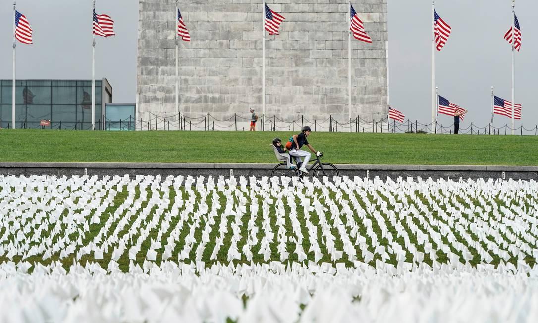 Ciclista pedala em frente a uma exposição de bandeiras brancas representando americanos que morreram de Covid-19, em Washington, EUA Foto: JOSHUA ROBERTS / REUTERS/17-09-2021