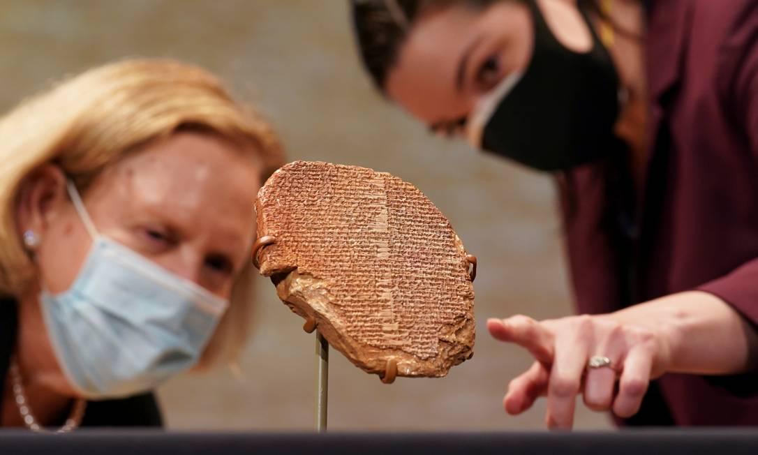 Pesquisadoras observam de perto tabuleta de Gilgamesh durante cerimônia de repatriação da obra para o Iraque, em Washington, EUA Foto: KEVIN LAMARQUE / REUTERS