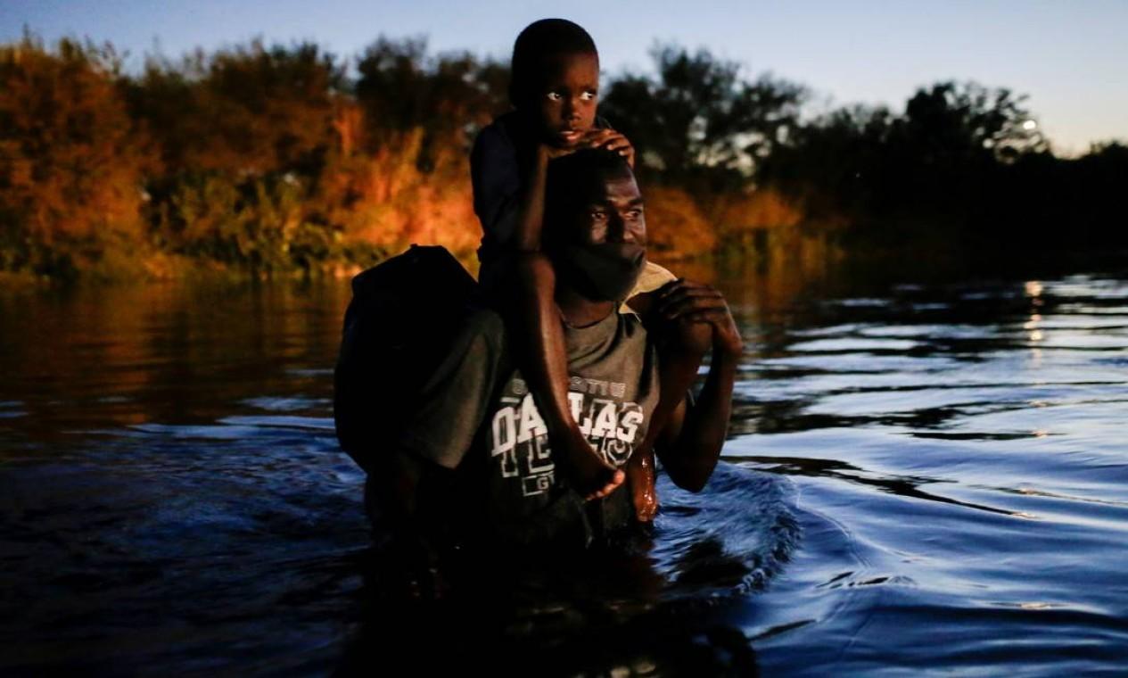 Migrante com seu filho nos ombros cruza o Rio Grande para procurar abrigo na fronteira entre Del Rio, no Texas, com Acuna, no México Foto: DANIEL BECERRIL / REUTERS