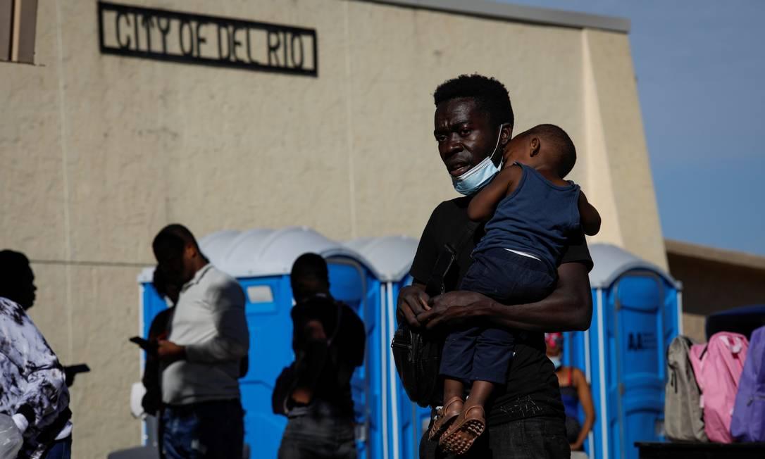 Um imigrante carrega uma criança enquanto espera na fila para embarcar em um ônibus para Houston, na cidade de Del Río, no Texas Foto: MARCO BELLO / REUTERS