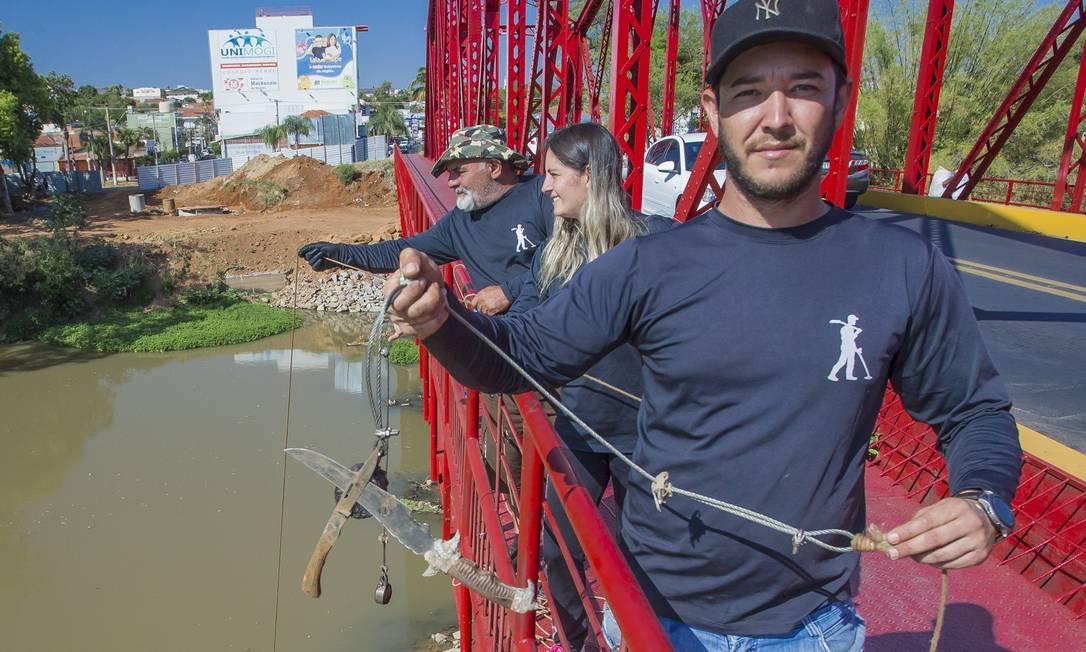 Acompanhado do sogro e da mulher, Moisés Pozzolini exibe facão pescado no Rio Mogi-Guaçu: hobby é exibido em perfil do YouTube Foto: Edilson Dantas / Agência O Globo