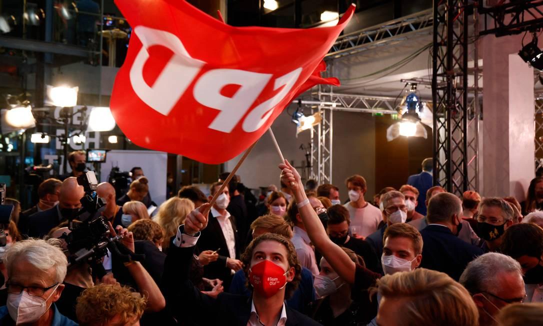 Eleirores agitam bandeiras dos social-democratas em evento do SPD após divulgação das pesquisas de boca de urna Foto: ODD ANDERSEN / AFP