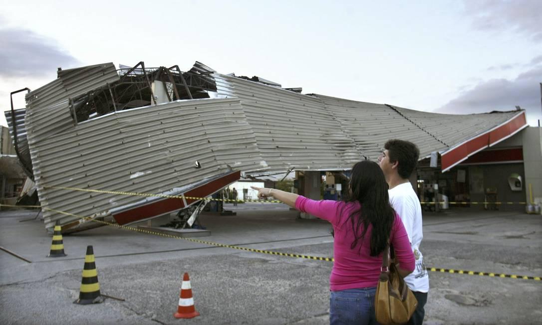 Moradores apontam para a cobertura de um posto de gasolina na cidade de Torres, em 29 de março de 2004. O posto foi danificado por um ciclone que se formou no Atlântico Sul e desembarcou no sul do Brasil. Foto: Paulo Whitaker / Reuters