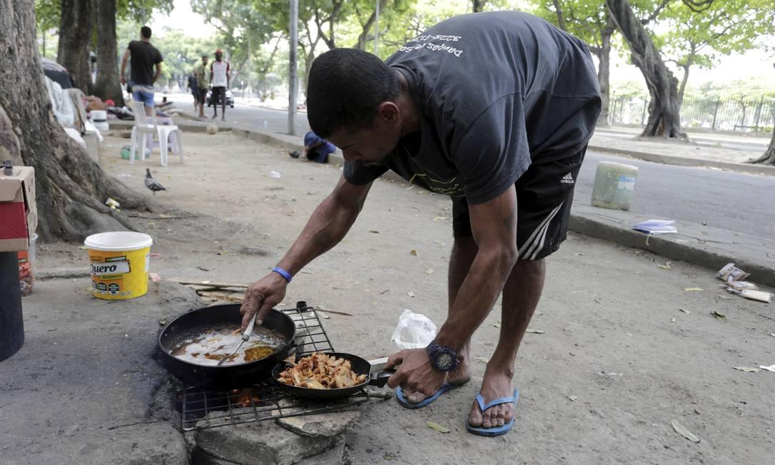 Luis Vander frita pelanca que pega no caminhão de osso Foto: Domingos Peixoto / Agência O Globo
