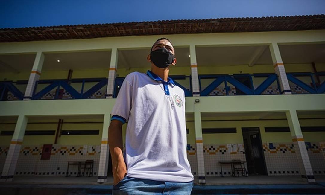 Alex Luick diante de Escola Estadual Fernandas Lima, em Maceió, que forneceu a calça jeans do uniforme para ele poder voltar às aulas presenciais Foto: Jonathan Lins / Agência O Globo