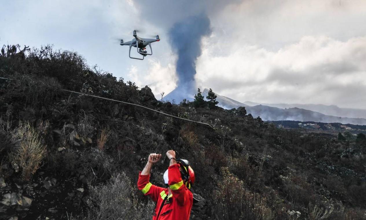 Membro da Emergência Militar Espanhola (UME) monitorando por drone o fluxo de lava do vulcão Cumbre Vieja retratado ao fundo, na ilha canária de La Palma Foto: LUISMI ORTIZ / AFP
