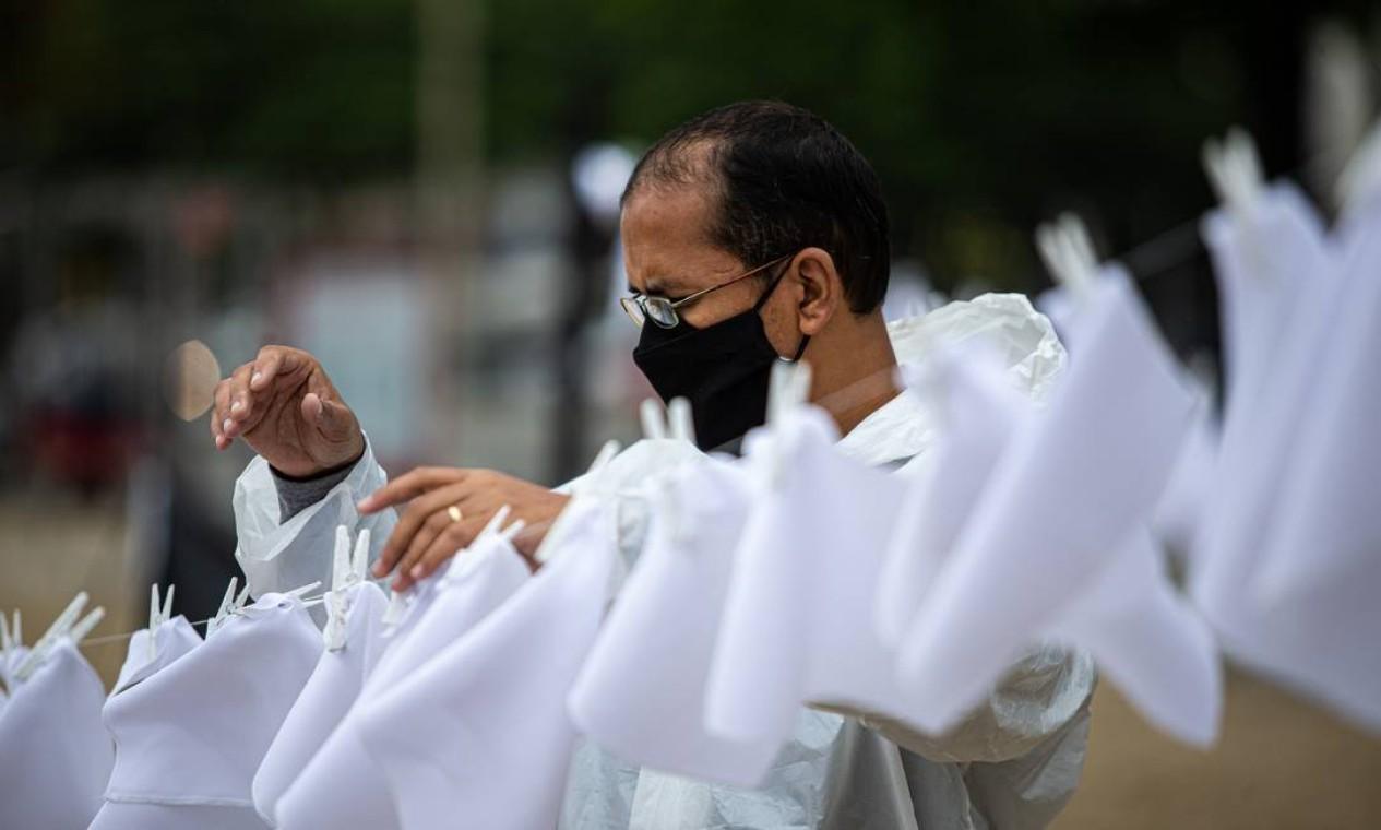 Ativista prega lenços brancos em varal para simbolizar as vítimas da pandemia no Brasil Foto: Hermes de Paula / Agência O Globo