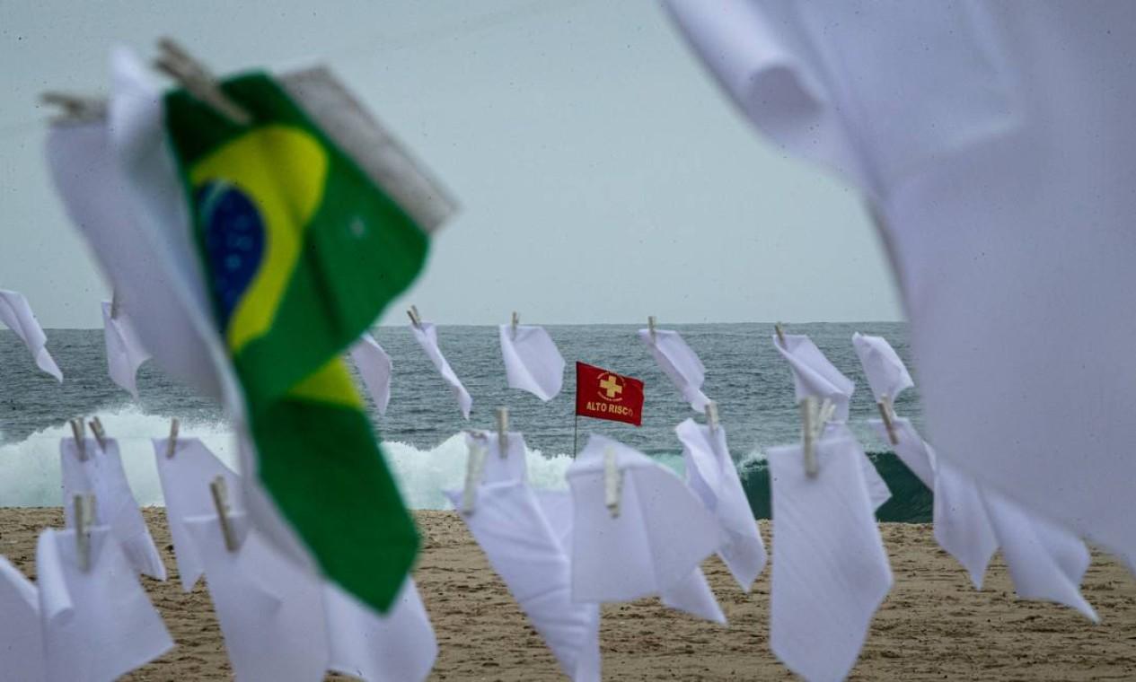 Alto risco. Bandeira de alerta de segurança para mergulho no mar é visto entre lenços brancos e a bandeira nacional em ato da ONG Rio de Paz Foto: Hermes de Paula / Agência O Globo