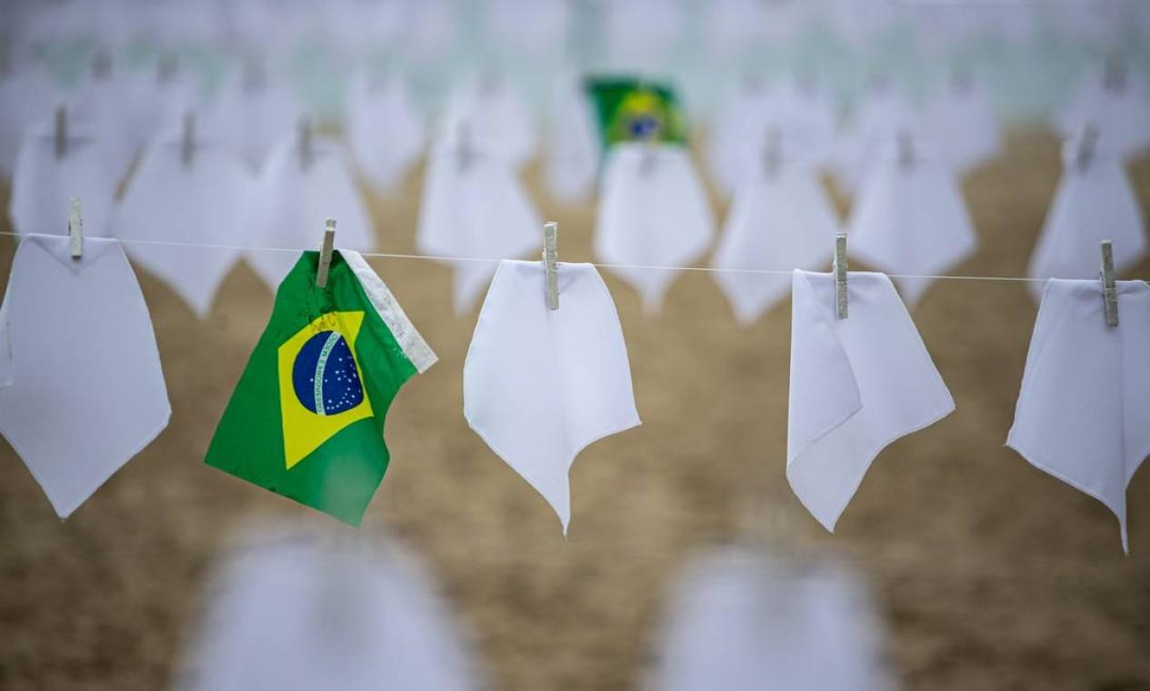 A organização não governamental estendeu em um varal na areia, em frente ao Copacabana Palace, com 600 lenços brancos Foto: Hermes de Paula / Agência O Globo