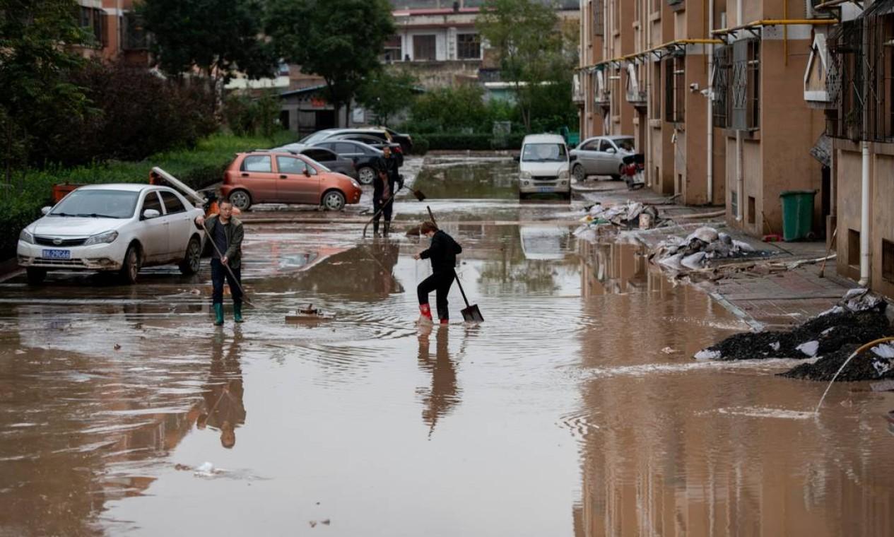 Moradores tentam fazer limpeza durante enchente na província de Shanxi Foto: STRINGER / VIA REUTERS