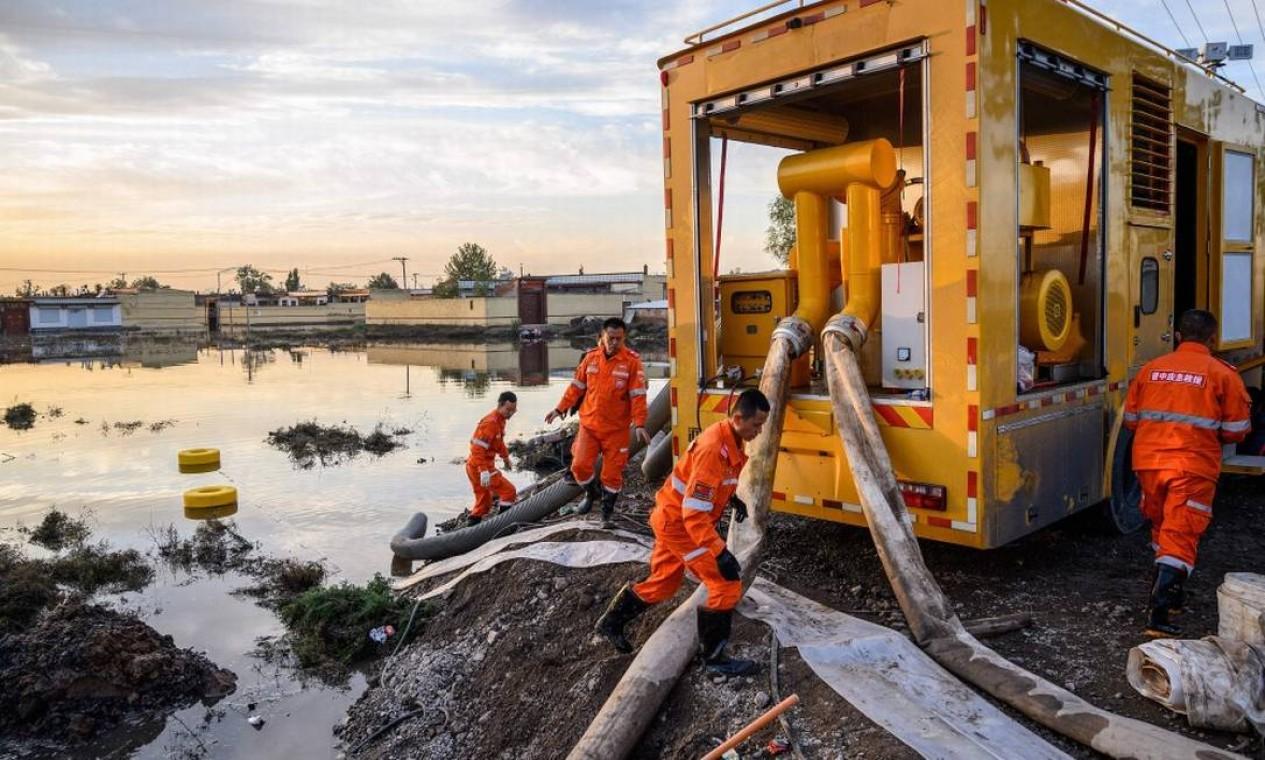 Funcionários bombeiam água que tomou cidade após chuvas torrenciais no Norte da China Foto: STR / AFP