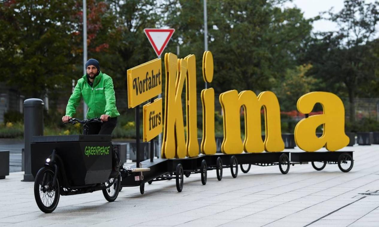 """Manifestante do Greenpeace dirige uma bicicleta com a mensagem """"prioridade para o clima"""", antes de uma reunião para negociações exploratórias para uma possível nova coalizão governamental, em Berlim, Alemanha Foto: ANNEGRET HILSE / REUTERS"""