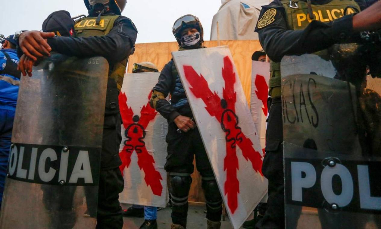 Policiais observam membros do Movimento Hispânico do Peru marchar no centro histórico de Lima, no Dia de Colombo, com a bandeira da Lâmina Borgoña em comemoração ao 529º aniversário da invasão do navegador Cristóvão Colombo à América Foto: GIAN MASKO / AFP