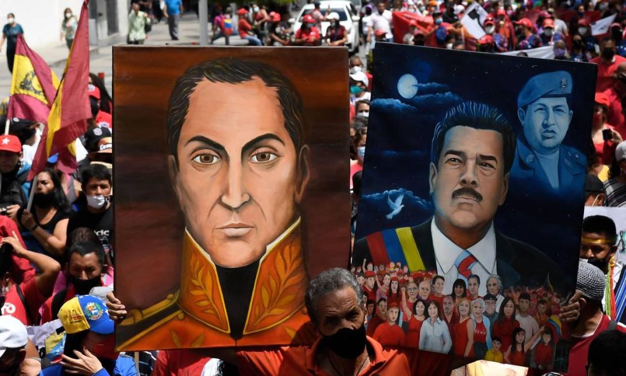 Aapoiador do presidente da Venezuela, Nicolas Maduro, mostra retratos dele e do herói libertador da Venezuela Simón Bolívar, durante marcha para comemorar o dia da Resistência Indígena, em Caracas Foto: FEDERICO PARRA / AFP