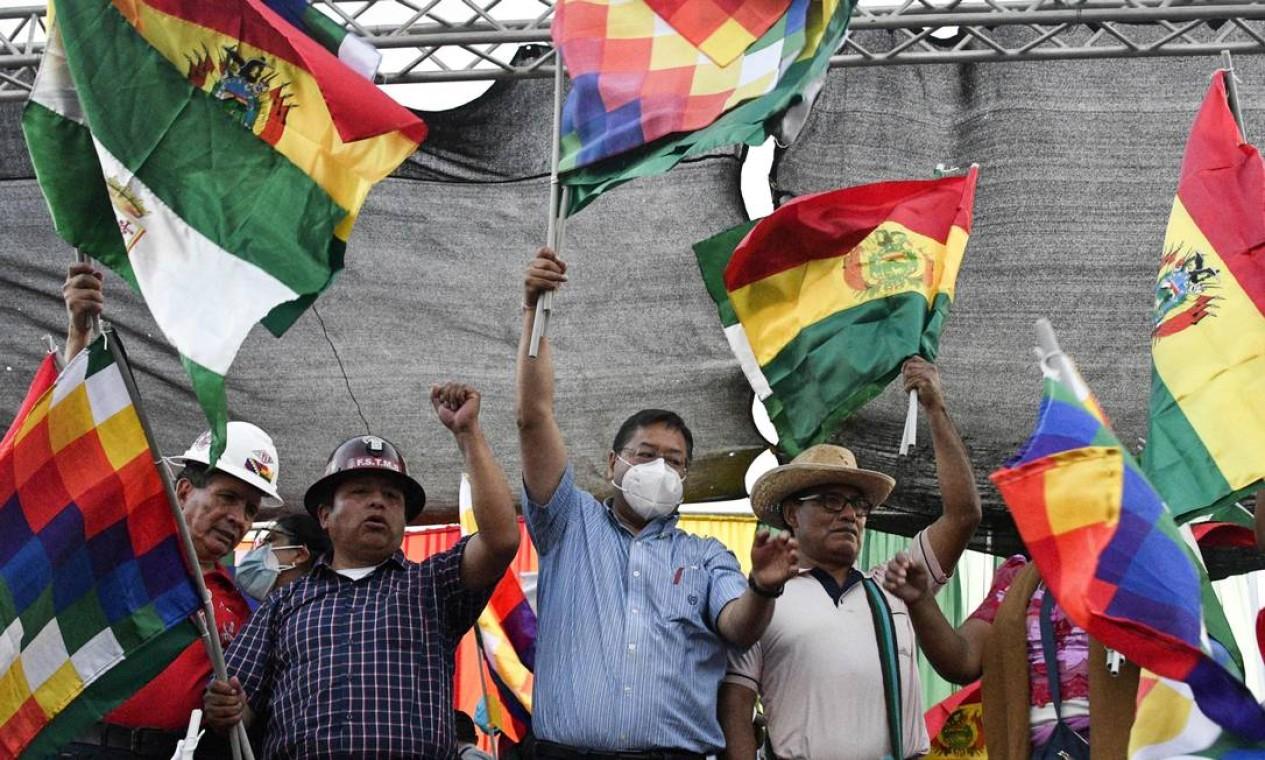 O presidente da Bolívia, Luis Arce, de máscara, agita bandeira de Whipala – que representa as nações nativas dos Andes – durante um comício pró-governo em Santa Cruz, Bolívia Foto: AIZAR RALDES / AFP