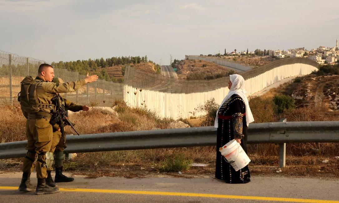 Una mujer palestina habla con un militar de las FDI en sus campos de olivos al otro lado del muro de separación israelí, después de obtener un permiso especial israelí para recoger olivos en Hebrón, Cisjordania, Foto: Hazem Bader / AFP
