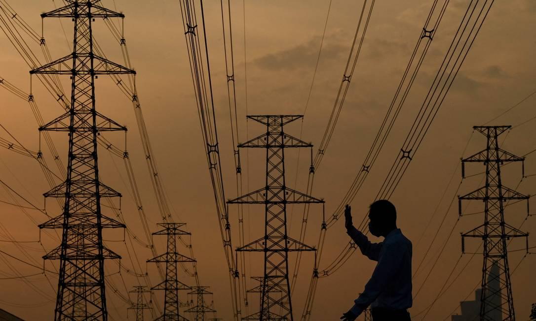 El asistente de estacionamiento hace gestos mientras se encuentra debajo de las líneas de tránsito en Beijing, China Foto: NOEL CELIS / AFP