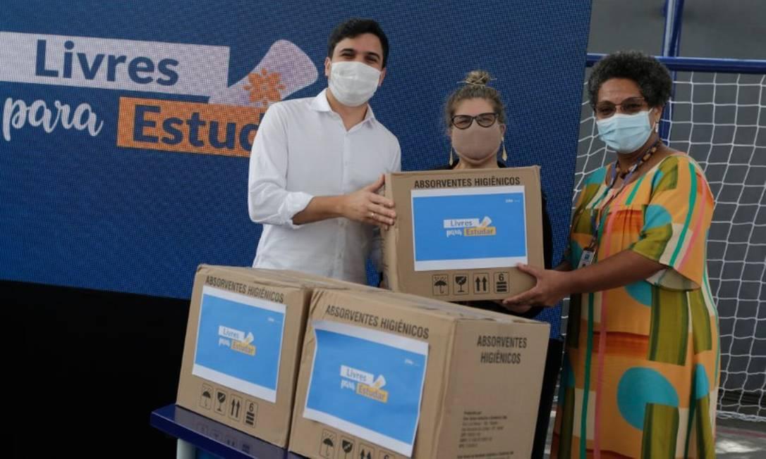O secretário de Educação, Renan Ferreirinha, entrega simbolicamente caixa de absorventes para a diretora da escola Lucimara Montalvani Spindola Foto: Márcia Foletto / Agência O Globo