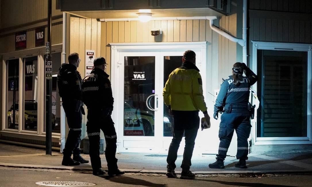 Policiais observam uma das flechas usadas no ataque, que ficou presa à fachada de uma loja, na cidade de Kongsberg, na Noruega Foto: TERJE PEDERSEN / AFP