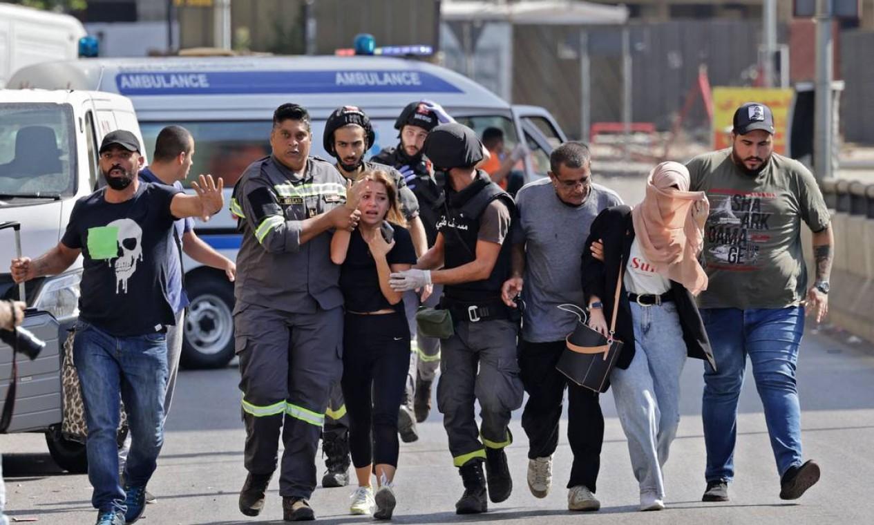 Médicos libaneses ajudam a evacuar civis durante confrontos na área de Tayouneh, no subúrbio ao sul da capital Beirute. Tiroteios mataram pelo menos três pessoas e feriram 20 Foto: JOSEPH EID / AFP