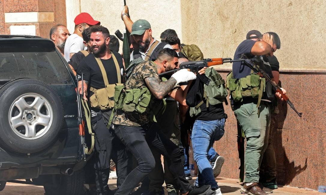 Combatentes do Hezbollah e do Amal participam de confronto no bairro de Tayoneh, no Sul de Beirute Foto: ANWAR AMRO / AFP