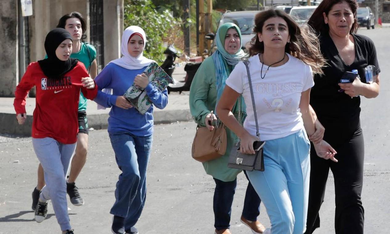 Civis evacuam suas casas durante confrontos na área de Tayouneh, no subúrbio ao sul da capital Beirute Foto: ANWAR AMRO / AFP