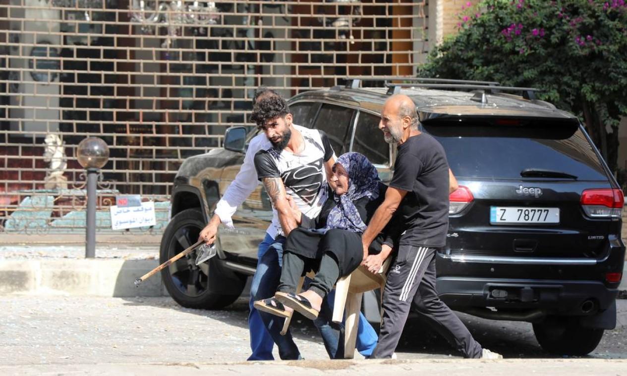 Homens ajudam a carregar uma mulher idosa após o início do tiroteio, em Beirute Foto: MOHAMED AZAKIR / REUTERS
