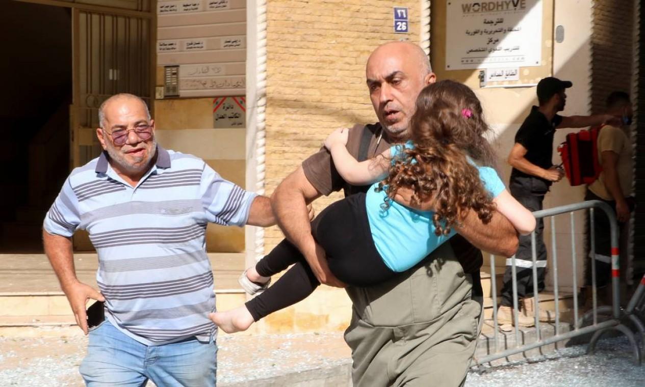 Homem carrega menina para tentar se proteger após o início do tiroteio Foto: MOHAMED AZAKIR / REUTERS