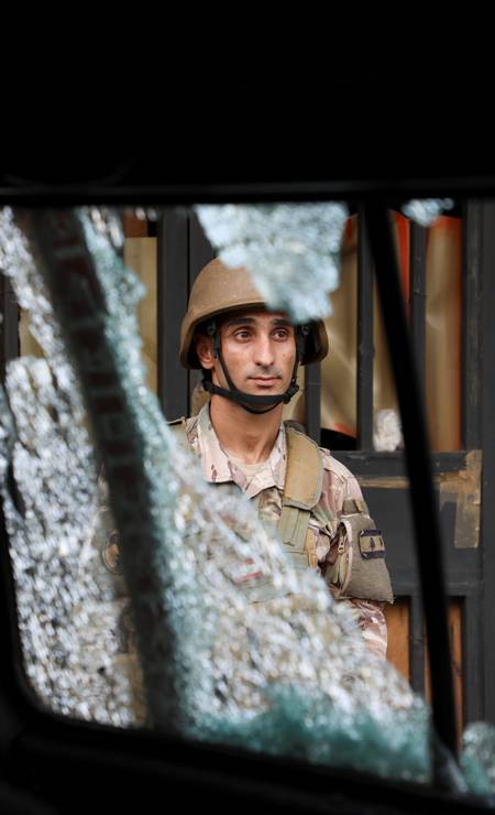 Soldado do exército é visto atrás de um vidro estilhaçado, após o tiroteio Foto: MOHAMED AZAKIR / REUTERS