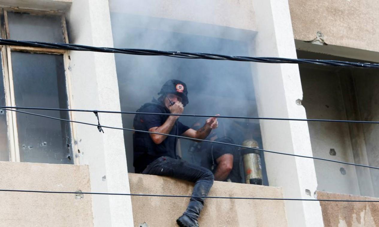 Membros da defesa civil tentam apagar um incêndio dentro de um prédio Foto: AZIZ TAHER / REUTERS