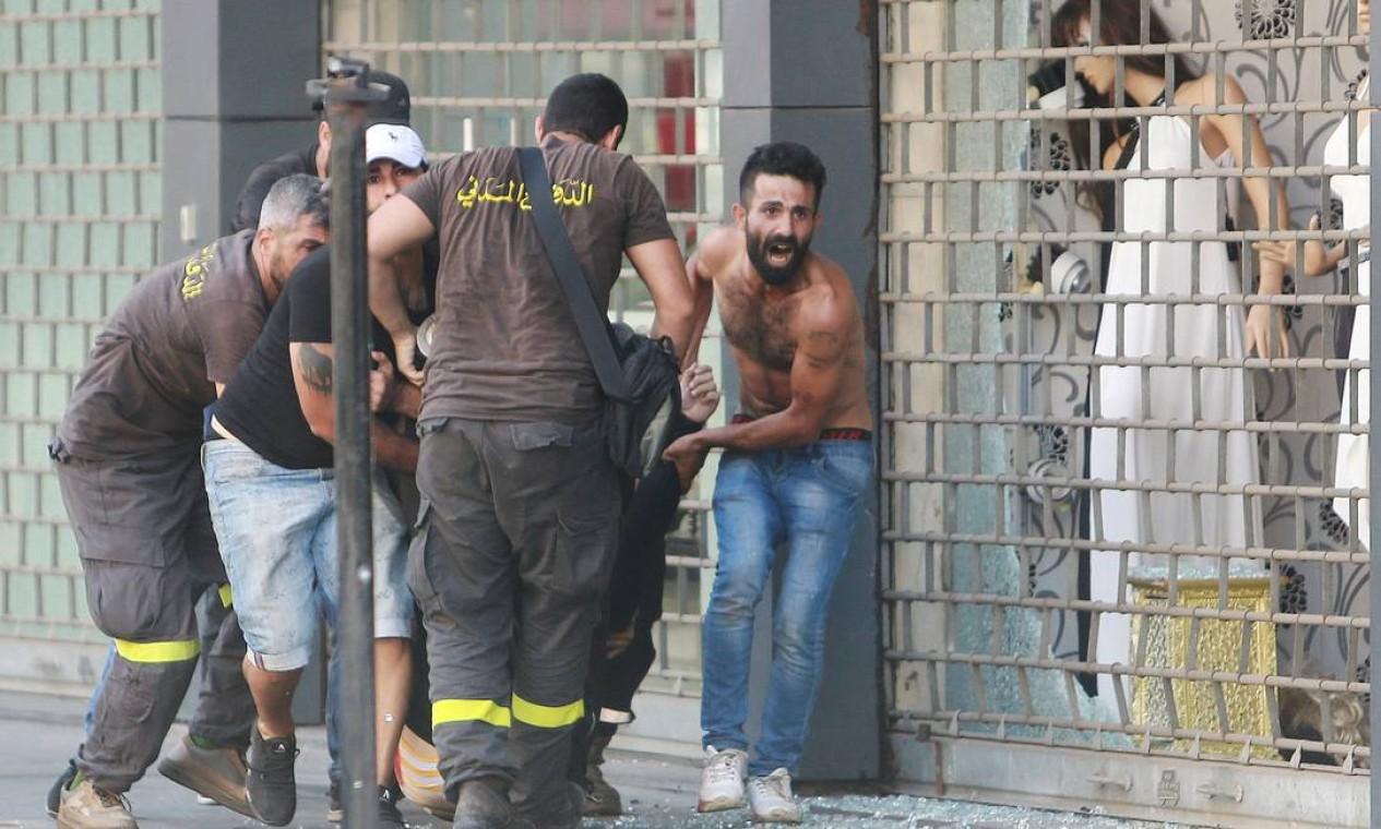 Civis socorrem pessoa ferida em tiroteio Foto: AZIZ TAHER / REUTERS