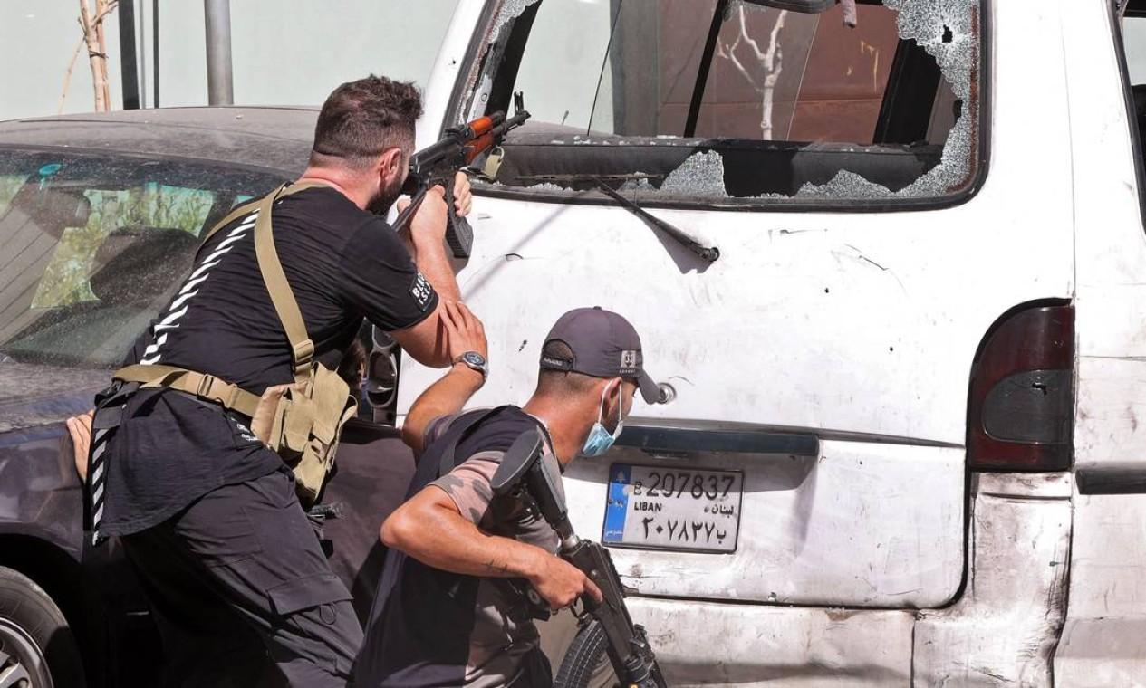 Guerrilheiros buscam abrigo atrás de van com vidros estilhaçados por tiros Foto: ANWAR AMRO / AFP
