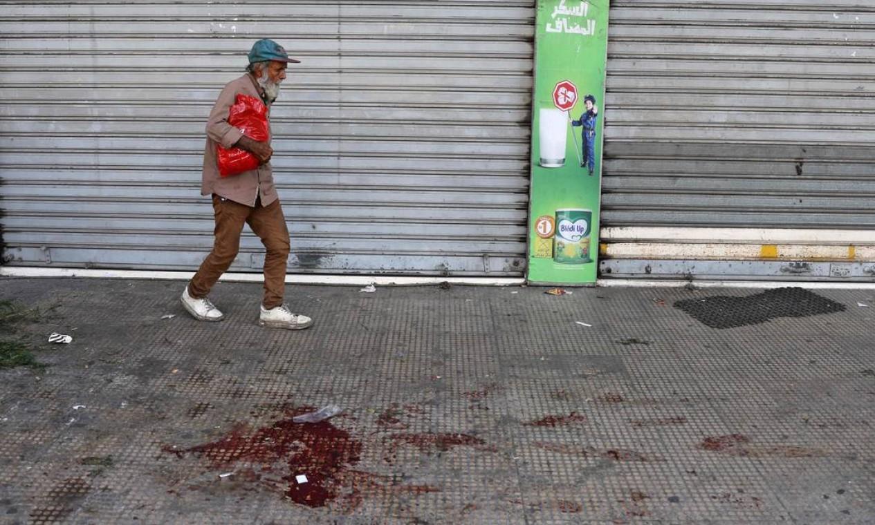 Idoso caminha perto de poça de sangue. Pelo menos, seis pessoas foram mortas em confrontos Foto: JOSEPH EID / AFP