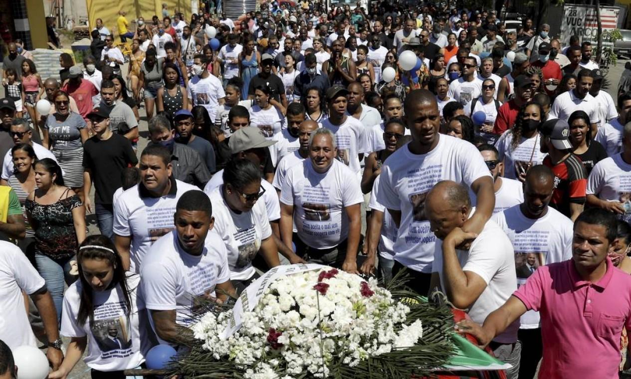 Com camisas personalizadas com a foto de Sandro, amigos e familiares cantam em conjunto enquanto seguem o cortejo Foto: Gabriel de Paiva / Agência O Globo