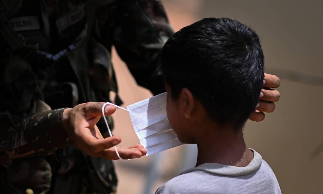 Membro das Forças Armadas coloca máscara em ciança, no Maranhão Foto: Andre Borges / NurPhoto via Getty Images