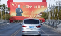 Veículo dirige em rua próxima ao Centro de Lançamento de Satélites de Jiuquan, diante de publicidade com a imagem do presidente chinês Xi Jinping Foto: CARLOS GARCIA RAWLINS / REUTERS