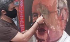 O artista Gustavo Burkhart recupera pintura com o rosto de Veríssimo Foto: Emanuele Quadros / Divulgação
