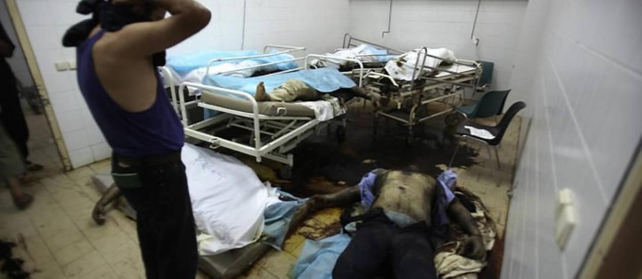 Homem observa corpos em decomposição em uma das salas de hospital abandonado no bairro de Abu Salim, em Trípoli: ao menos 50 cadáveres encontrados no local - AFP